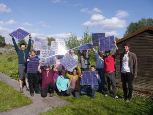 Group of people smiling, holding solar panels